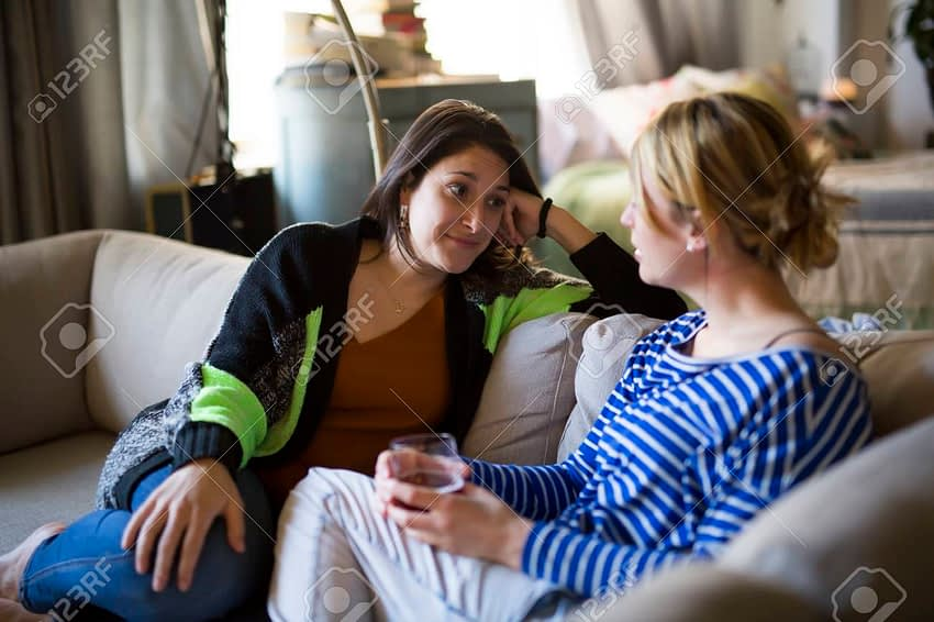 85395245 people relations two girls are speaking with emotions sitting on sofa